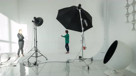 atirar : Timelapse shot of professional photographer and woman model having photo shoot in studio Stock Footage