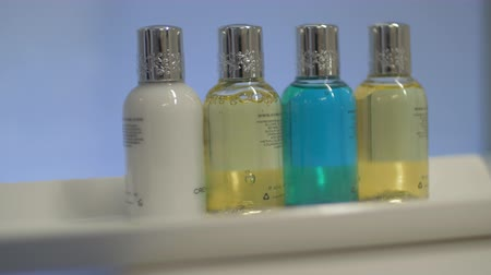 şampuan : Close-up shot of housekeeper placing set of four bottles in the hotel bathroom. Shampoo, hair conditioner, body wash and lotion Stok Video