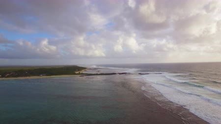 lave : Aerial view of water line of sea waves with foam and rugged coast line against blue sky with clouds, camera moves up, Indian Ocean, Mauritius Island Stock Footage
