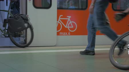 modern train wagon : Bottom view of peoples legs, that going in and out the train in the subway station, modern orange wagon, where man can rides with bikes, Frankfurt am Main, Germany Stock Footage