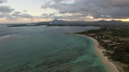 lave : Aerial view of rugged coast line of Mauritius Island, water laves sand strand, cloudy sky, forests and hills against sky and clouds in Indian Ocean Stock Footage