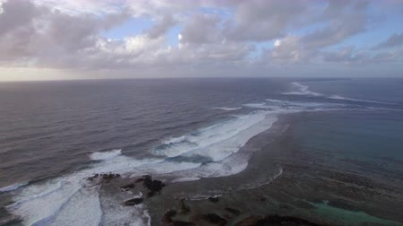 lave : Aerial view of water line of seas that do not mix and rugged coast line against blue sky with clouds, Indian Ocean, Mauritius Island