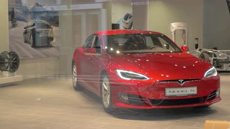tesla model s : FRANKFURT, GERMANY - JULY 01, 2016: Modern red sedan Model S exhibited in Tesla Store. View through the glass of shop-window. American automaker specializing in electric cars