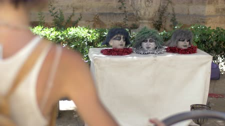 travessura : VALENCIA, SPAIN - JULY 15, 2016: Little boy running up to the table with heads in and being frightened. Street actors entertaining people. Real sound included