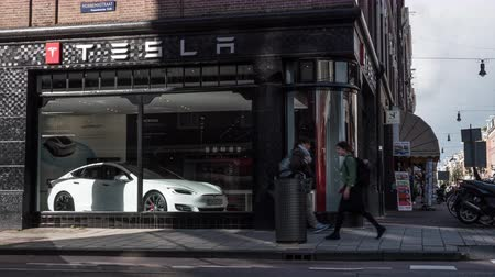 auto show : AMSTERDAM, NETHERLANDS - AUGUST 09, 2016: Timelapse shot of transport and people traffic on the street near Tesla Store. American automaker and energy storage company founded in 2003