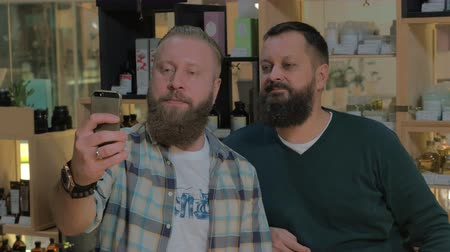 broda : Two mature bearded men taking cellphone selfie in the barbershop