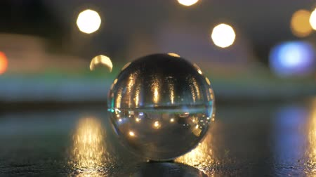 aberração : View of glass sphere imaging inverted cityscape with traffic road against blurred bokeh background in the evening