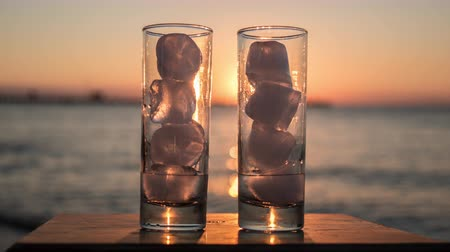 Timelapse close-up shot of two glasses with melting ice on the background of sea and sunset