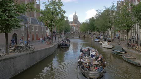 amsterodam : AMSTERDAM, NETHERLANDS - AUGUST 09, 2016: Comfortable water travel by touristic ship with cafe. City view with streets and canal
