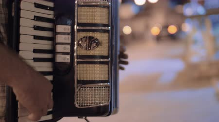 piano parts : Man playing piano accordion in evening city street and getting money from passer-by