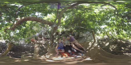 margem do rio : 360 VR video. Mother, father and son relaxing on wooden deck under the trees on riverbank. They playing game on tablet computer and having good time together in the wood Stock Footage