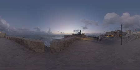 akko : 360 VR video. Acre view in late evening. Old coastal city with houses, ancient walls and active lighthouse. Man tourist walking in the street Stock Footage
