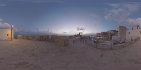 akko : ACRE, ISRAEL - MARCH 13, 2017: 360 VR video. Evening view of ancient coastal city with houses and active lighthouse on the South-West corner of the city ancient walls. One of the oldest cities in the world inhabited since the Middle Bronze Age some 4000 y