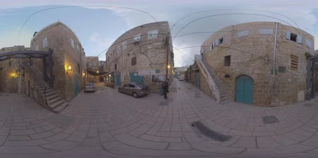 akko : ACRE, ISRAEL - MARCH 13, 2017: 360 VR video. Evening view of narrow street with old stone houses, several cars and vendor. One of the world oldest cities, continuously inhabited since the Middle Bronze Age some 4000 years ago