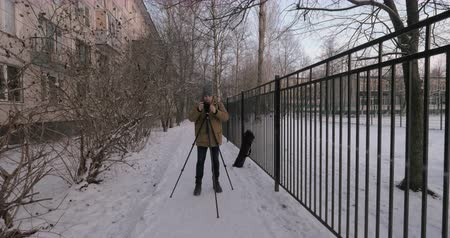 rögzített : Man coming up to the camera fixed on tripod and preparing to take photos or shoot video in winter street Stock mozgókép