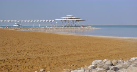 小屋 : Scene of the resort on Dead Sea. Beach and water view with few people relaxing under the shed in distance