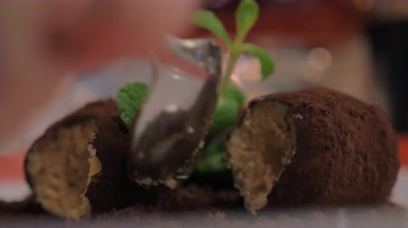 kekler : Close-up shot of eating a dessert in the restaurant. Sweet balls with cocoa coating, chocolate soil and mint Stok Video