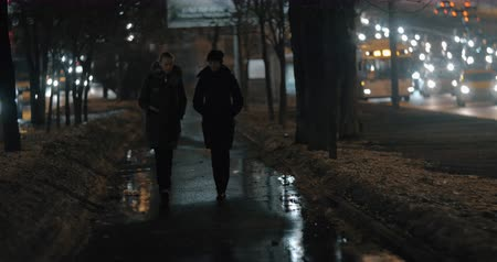 discutir : Sidewalk in dark winter city and two women friends walking and having a talk