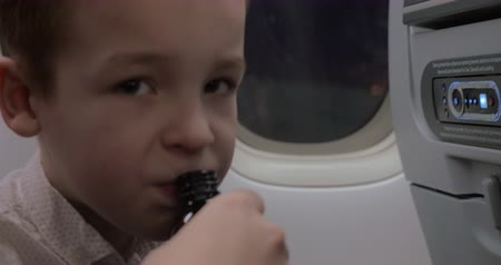 давать : Close-up shot of a boy doesnt want to take medicine that mother giving him in plane. He refusing with displeased look