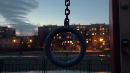 мрачный : Swinging sports ring and a mulistorey house with window lights in background. Evening shot