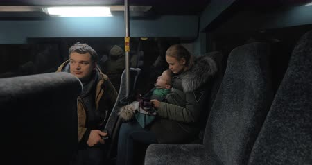 minibus : Family of three traveling by bus in winter evening. Man making photo of his wife and son playing on cell during the ride