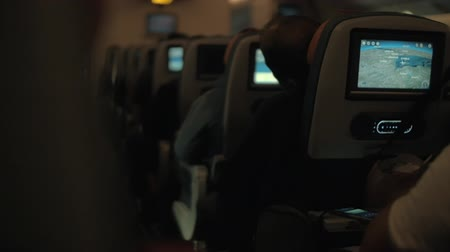 cabins : Slow motion shot of passengers following airplane route using the seat monitor map during night flight. View to the cabin with row of seats