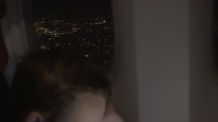 gece vakti : Slow motion shot of plane flying over city illuminated at night with following view to the kid spending time before landing with tablet PC Stok Video