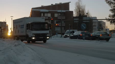 finlandês : ROVANIEMI, FINLAND - JANUARY 06, 2017: Slow motion shot or cars driving in snowy streets of the city at sunset. Warm light of evening golden sun