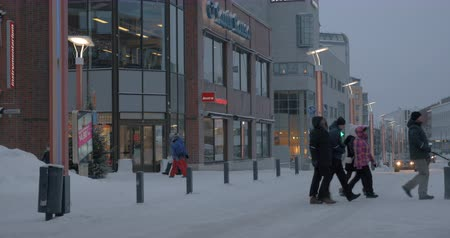 finlandês : ROVANIEMI, FINLAND - JANUARY 06, 2017: Cityscape of winter city with view to car traffic in the street with stores and people crossing the road Stock Footage