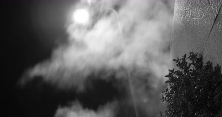 мрачный : Black and white gloomy and mystic shot of steam spreading outside at night in the light on street lantern