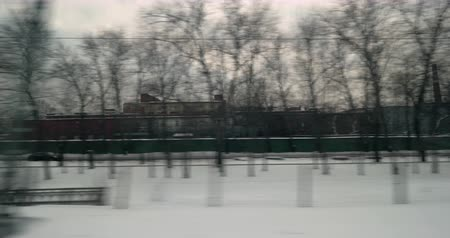 Timelapse shot of train ride in winter city. Viewing industrial facilities, houses, bare trees and snow banks when leaving Moscow 影像素材