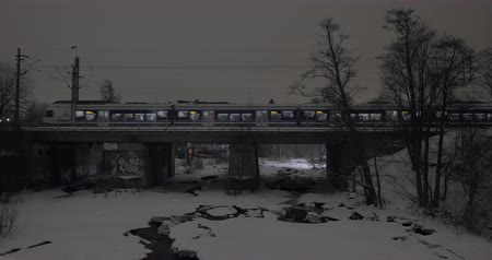 Modern commuter train crossing the bridge in the city. Scene in late winter evening