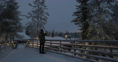 Man tourist taking mobile shots of snowy landscape with high pines on winter resort at night 影像素材