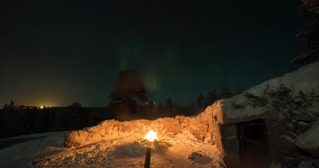 Timelapse shot of northern lights in night sky. Viewing natural phenomenon from the ground near the fire