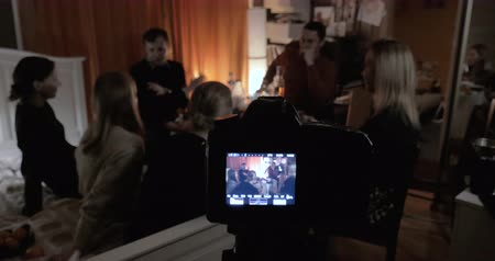 Camera taking video of friends meeting. People relaxing and talking during home party