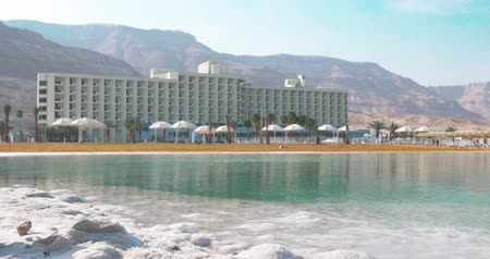 Scene with resort on Dead Sea. Hotel building on mountains background. Recreation area with pure water and salt beach