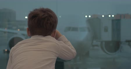 Child at the airport. He looking out the window and trying to see the plane served for boarding 影像素材