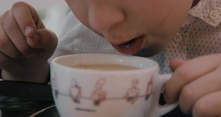 Close-up shot of a child blowing on the cup of hot tea with milk trying to cool it