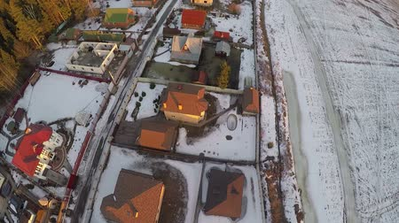 settlement : Flying over private houses and snowy farmland in small Russian township. Winter scene