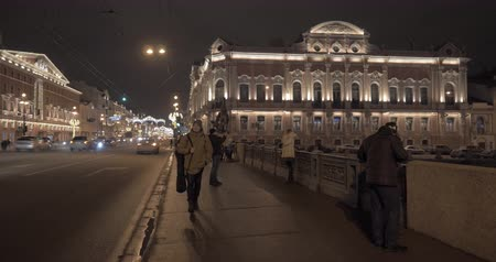 nevsky : Night view of illuminated Nevsky Prospect with transport traffic and people walking across Anichkov Bridge, man passing by the camera. Saint Petersburg, Russia