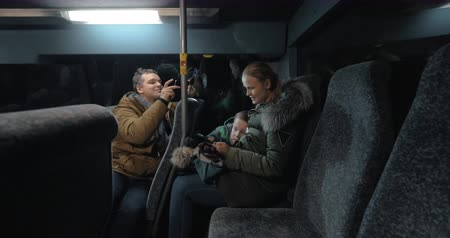 minibus : Man with cell taking video of woman with son playing on smart phone while traveling by bus in the evening