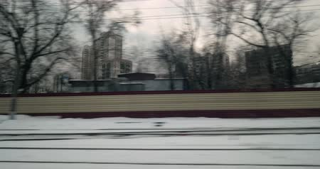 dojíždění : View from the window of a train traveling through the city in winter. Passing by the houses and industrial buildings, Russia