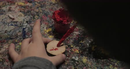 sanat : Close-up shot of a child painting a small wooden cut in red color. Handicraft activity Stok Video