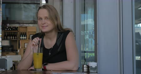 wistful : Young woman with dreamy look relaxing in cafe and drinking orange juice. She is deep in her thoughts
