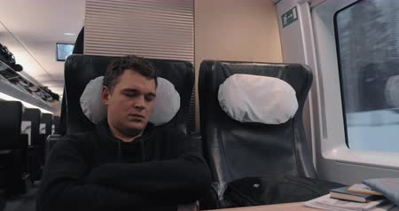 first class : Man is tired and falling asleep during the travel by first class in express train