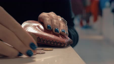cüzdan : Close-up shot of woman taking change from the purse and counting the last money she has