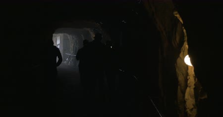 mijnwerker : Group of pit workers leaving the mine. The walking along the dark tunnel to the exit