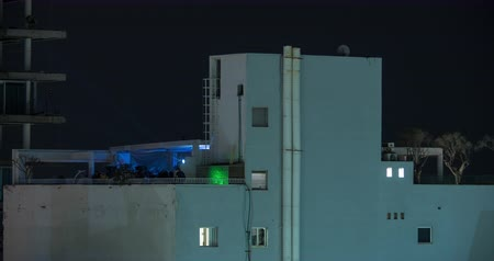 izrael : Timelapse night shot of people dancing at party with colour music taking place on the rooftop of multistorey house. Tel Aviv, israel