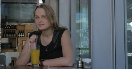 wistful : Cinemagraph - Young wistful woman relaxing in cafe and stirring fruit juice with a straw Stock Footage