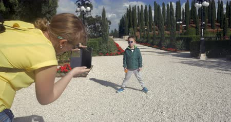 akko : ACRE, ISRAEL- MARCH 12, 2017: Woman tourist taking mobile photo of the son during the visit to Bahai gardens. People with model release